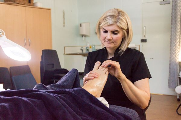 Female adult student giving a reflexology massage to a client