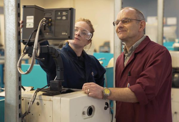 Teacher instructing student on how to use engineering workshop equipment