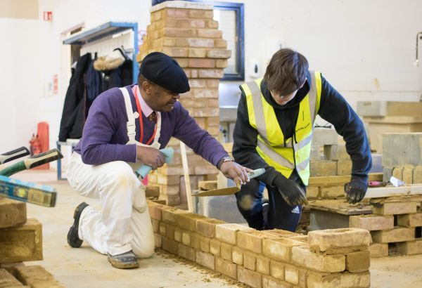 Student and teacher working on bricklaying