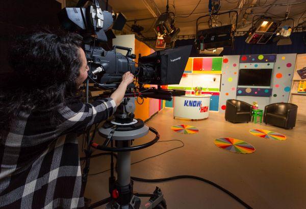 student-using-filming-equipment-in-TV-studio