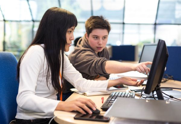 two students working together both on computers
