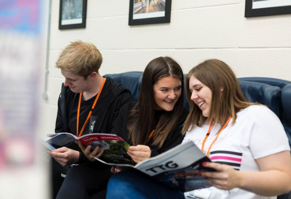 3 students one male two female sitting in aircraft seats reading aeroplane example magazines