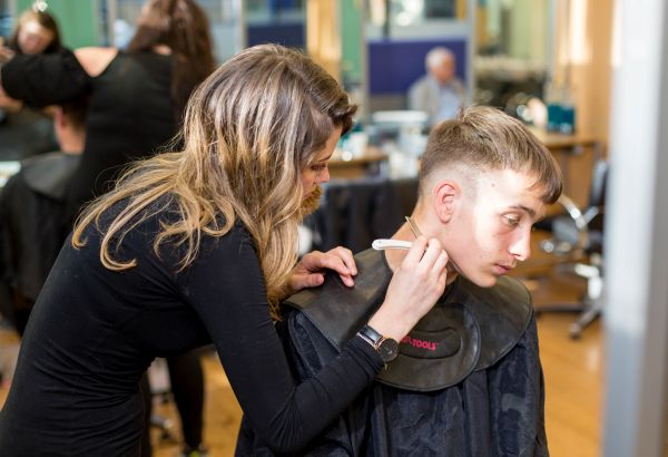 Barbering student giving a client a haircut