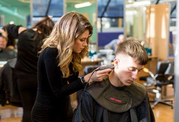 Barbering student cutting a client's hair