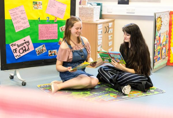 two female students sat on teaching classroom floor reading children's books