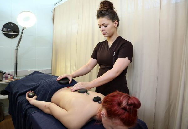 Student giving a stone therapy massage