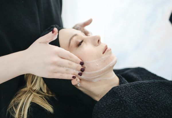 Student giving a client a facial