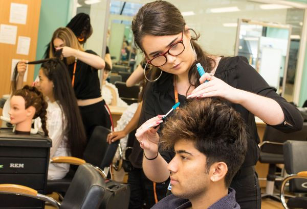 Barbering student cutting her client's hair