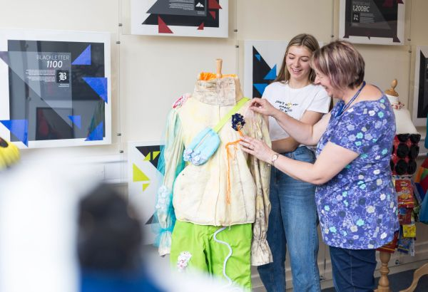 Fashion student and lecturer pinning designed clothes on manikin