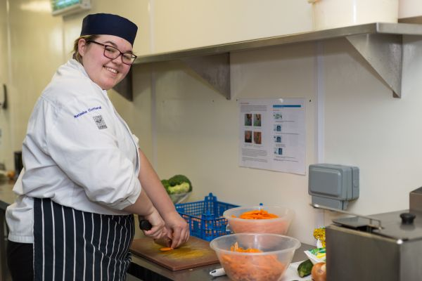 Catering student cutting carrots