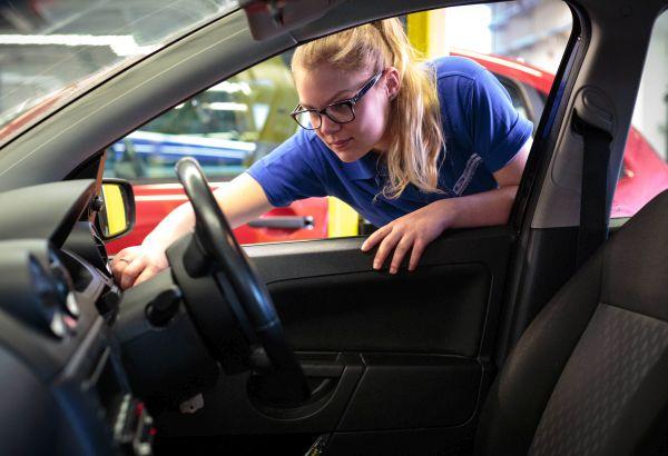 Motor vehicle student checking a car interior