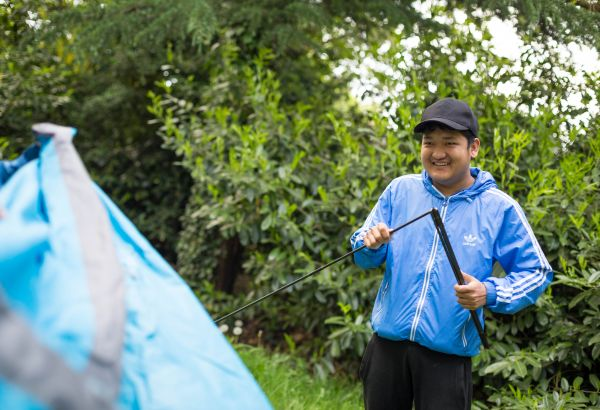 Public service student helping put up a tent