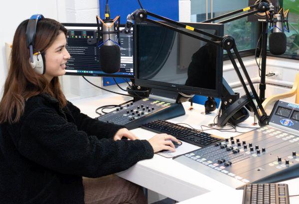 Media student sat in the college radio studio