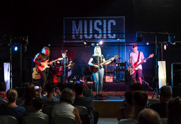 Group of music students performing live on stage