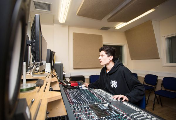 Music student sat working in the mixing room