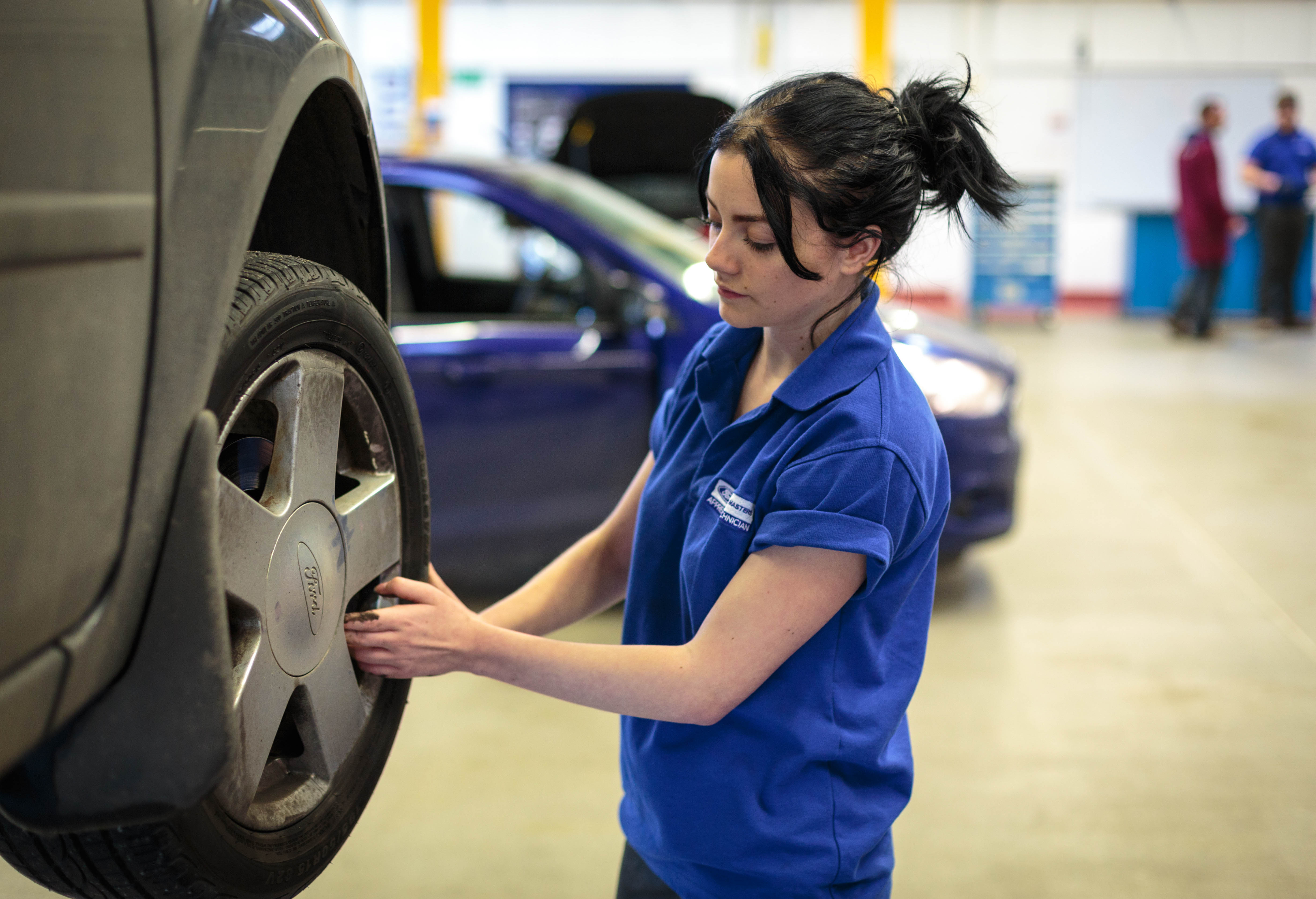 Student checking car tyre