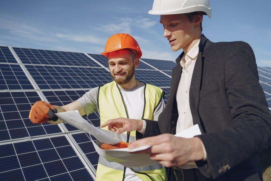 Two men stood besides a solar panel
