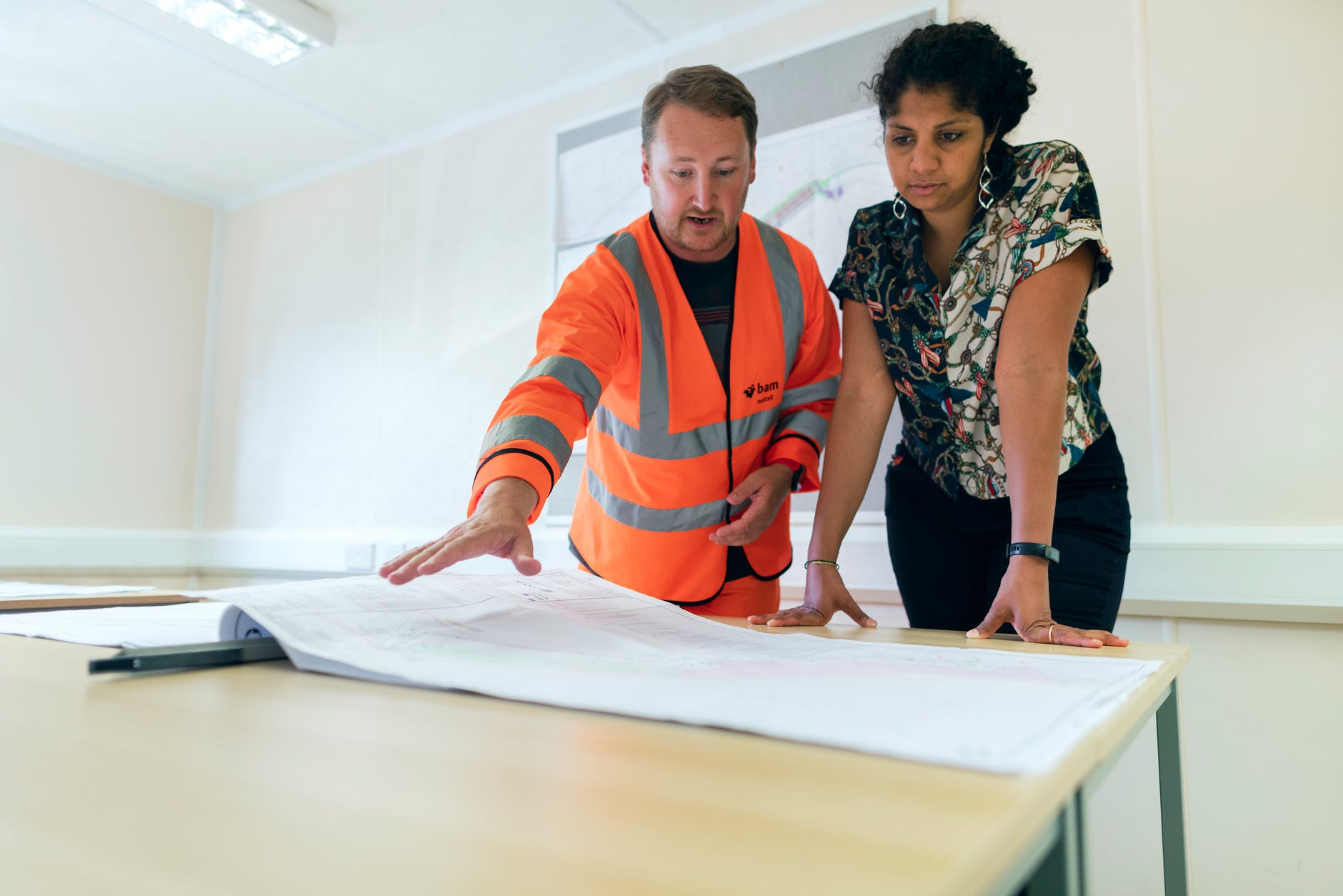 Man and women stood discussing building plans