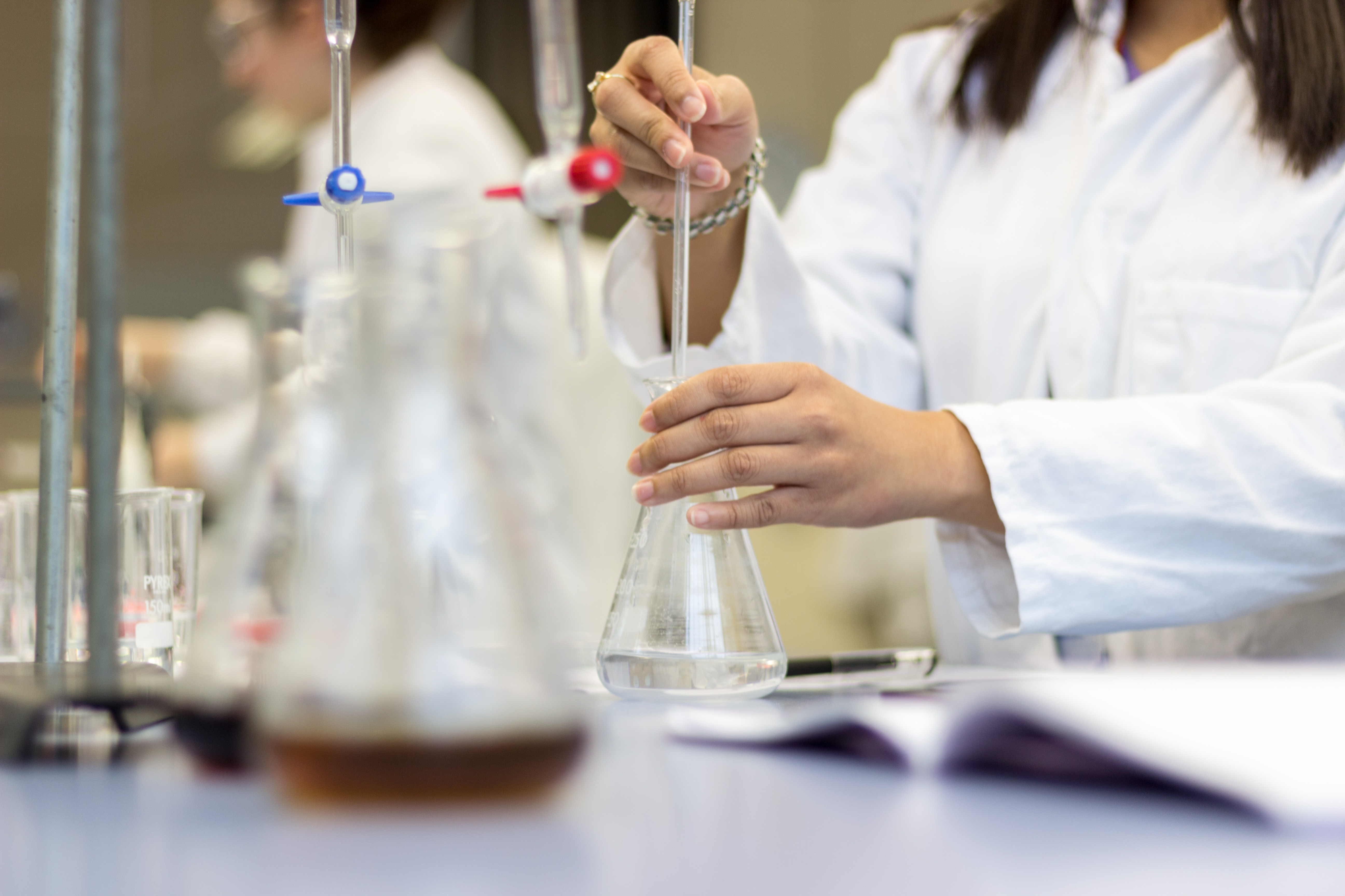 Girls working in the Science laboratory pouring chemicals
